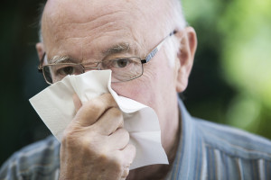 senior mit taschentuch putzt sich die nase