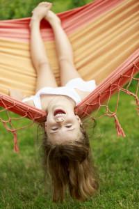 Summer fun - lovely girl playing in hammock